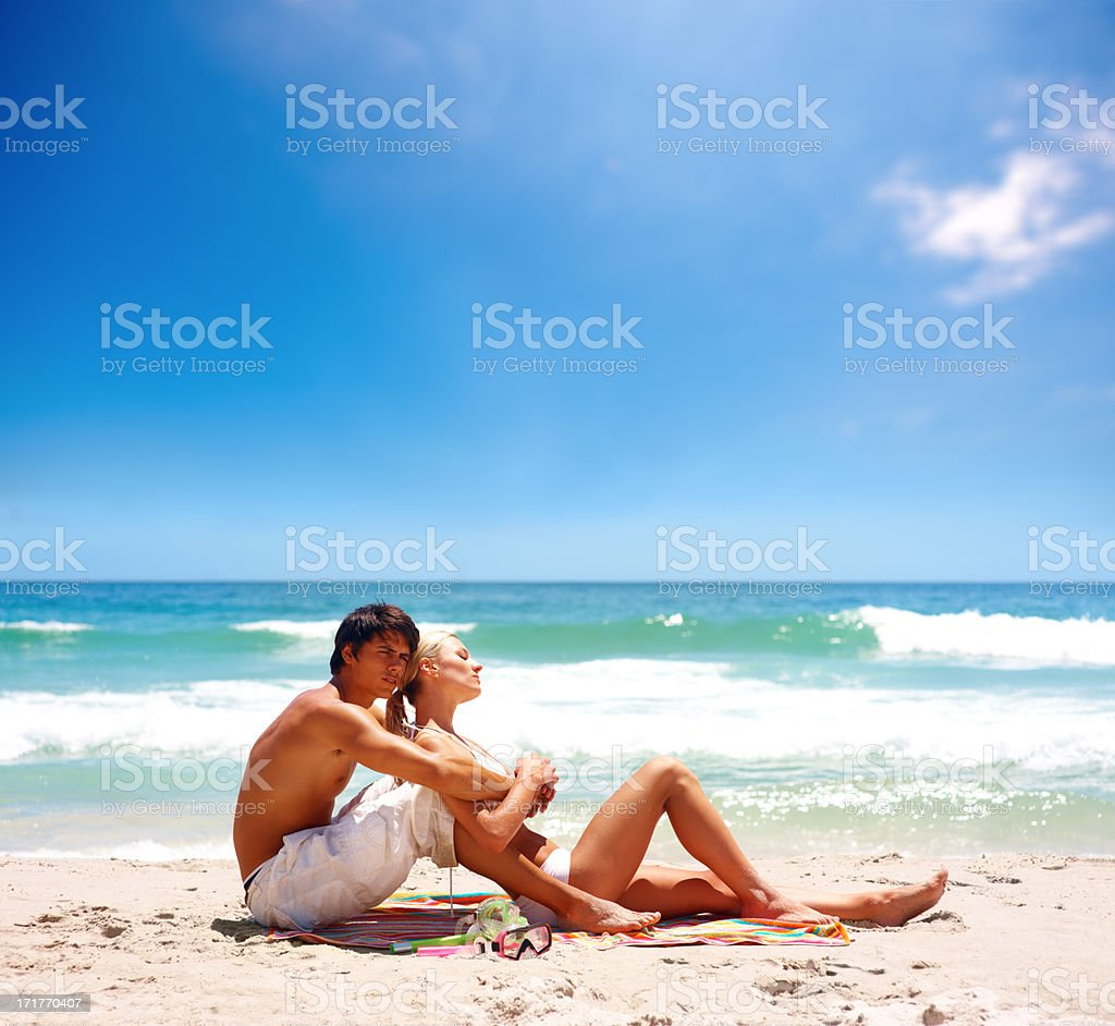Lovely couple relaxing together at the sea shore stock photo
