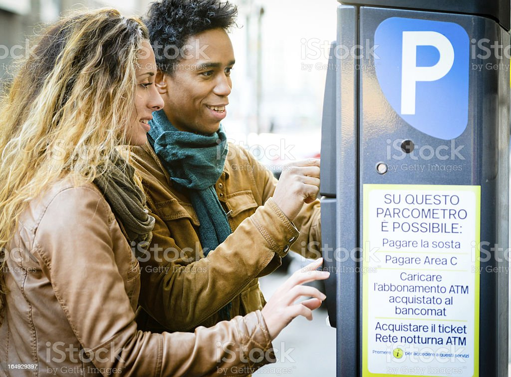 Lovely couple using parking ticket machine in the city stock photo