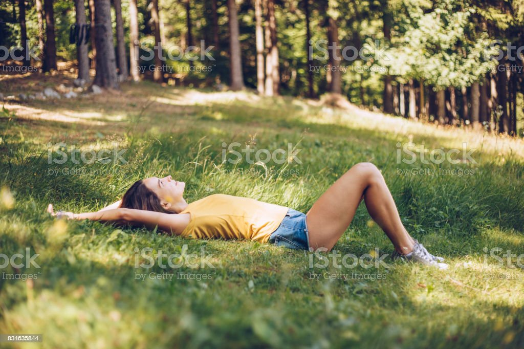 Young woman lying down in a grass. Enjoying in summer day.