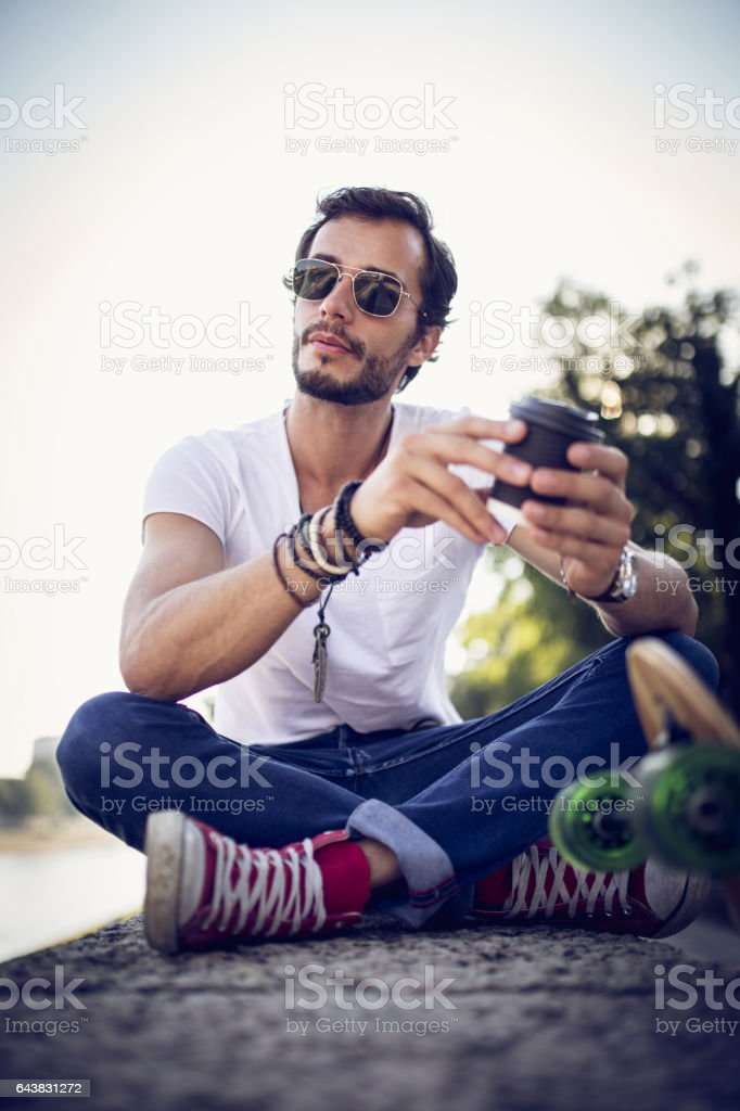 One man, holding coffee cup, sitting by his longboard.