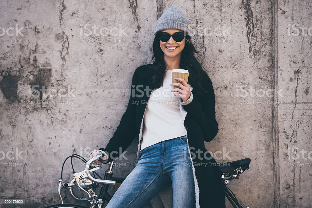 Beautiful young woman in sunglasses holding coffee cup and looking at...