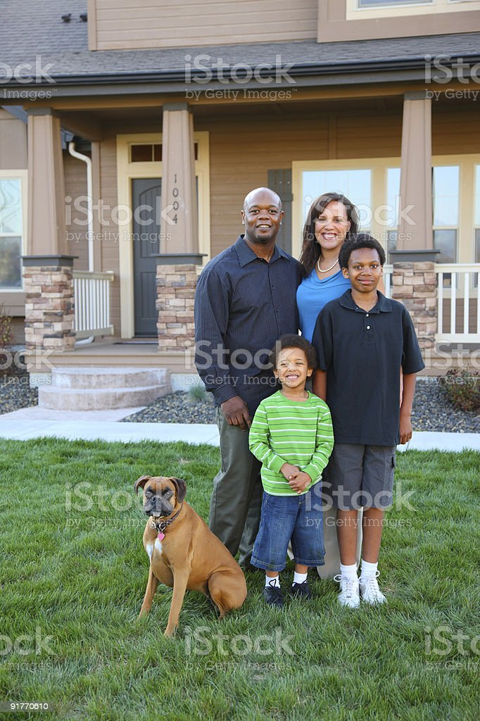 Lovely family of four with dog outside their dream home royalty-free stock photo