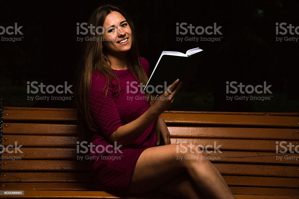 Lovely girl in a purple dress reading interesting  book stock photo