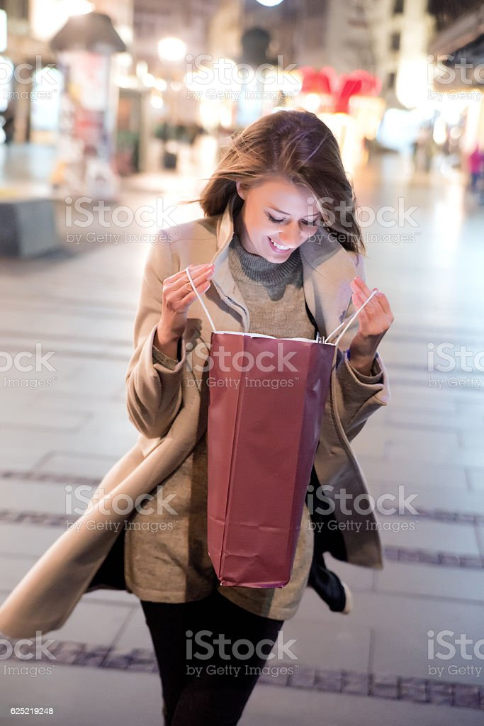Lovely girl looking at christmas  shopping bag during christmas stock photo