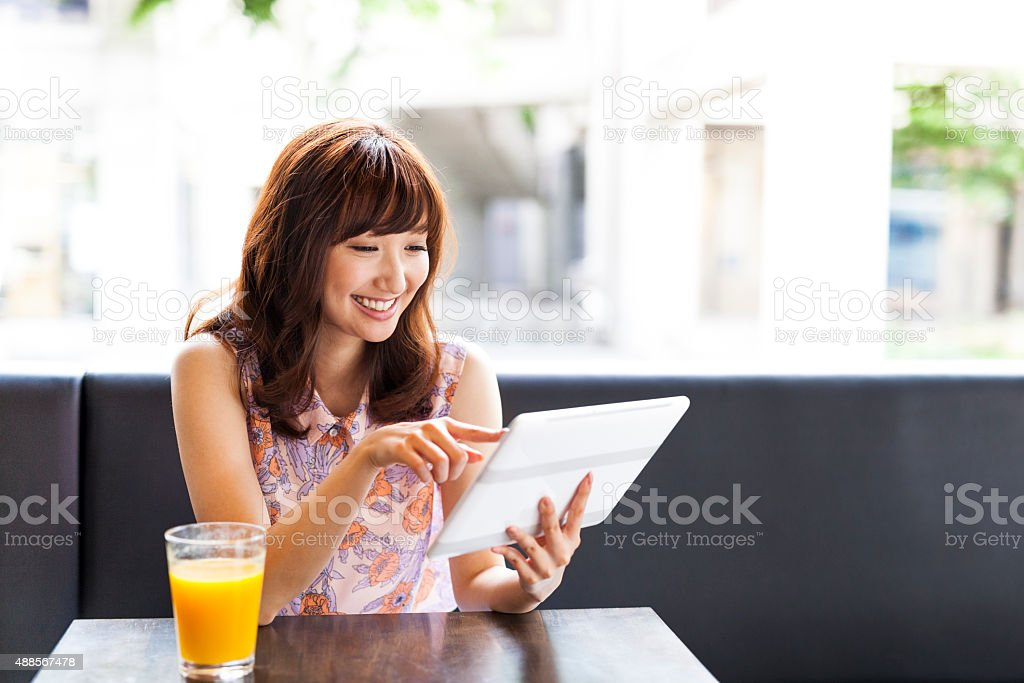 Lovely girl using ipad in a cafe stock photo