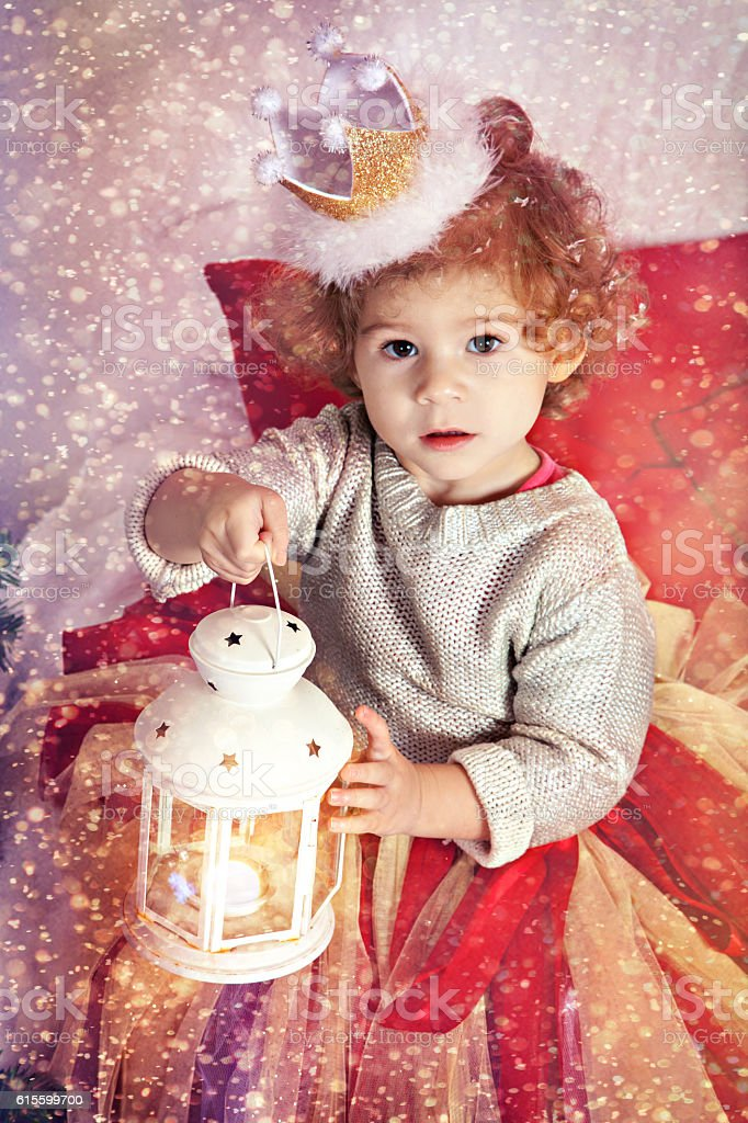 Lovely girl with magic lantern in Christmas Room stock photo