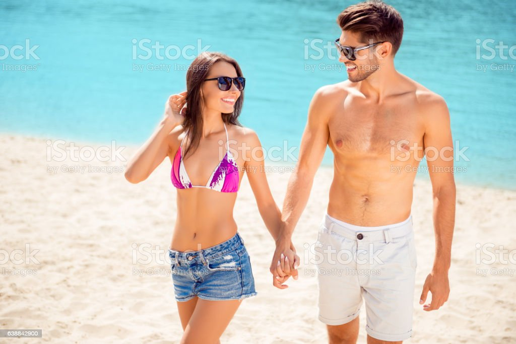 Lovely happy couple walking on tropical beach stock photo