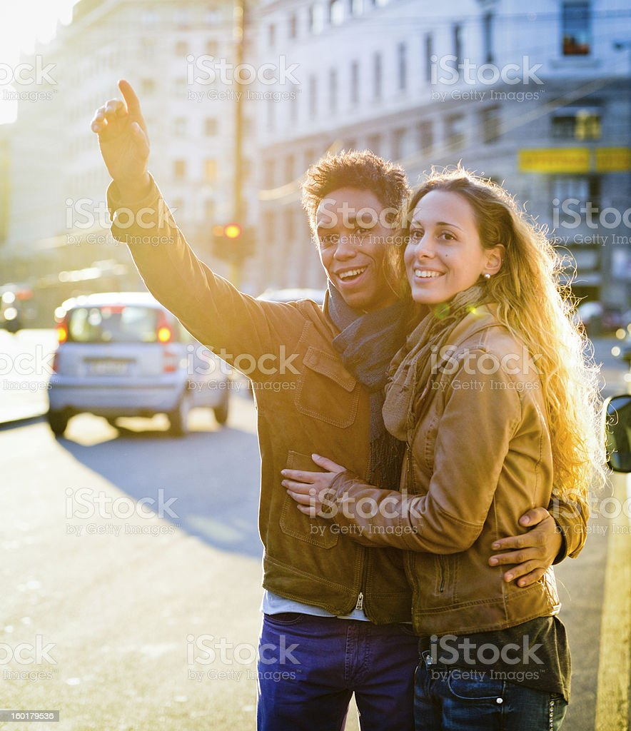 Lovely interracial couple hailing taxi on Milan street royalty-free stock photo
