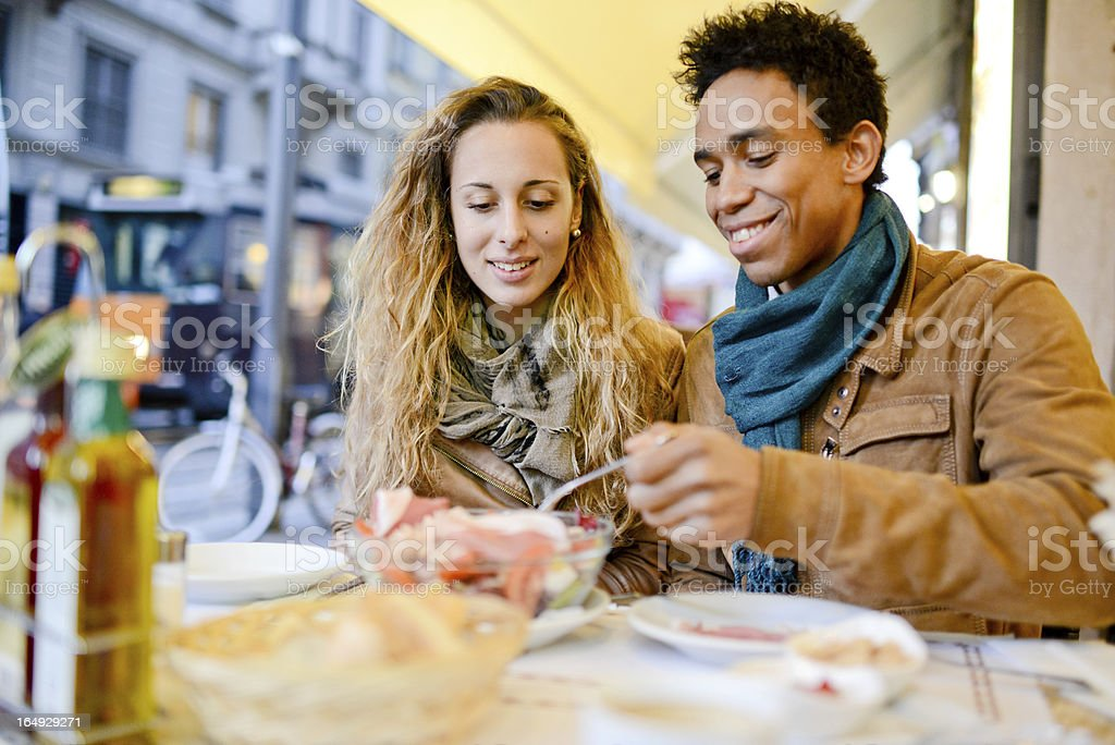 Lovely interracial couple having lunch at outdoors cafe royalty-free stock photo