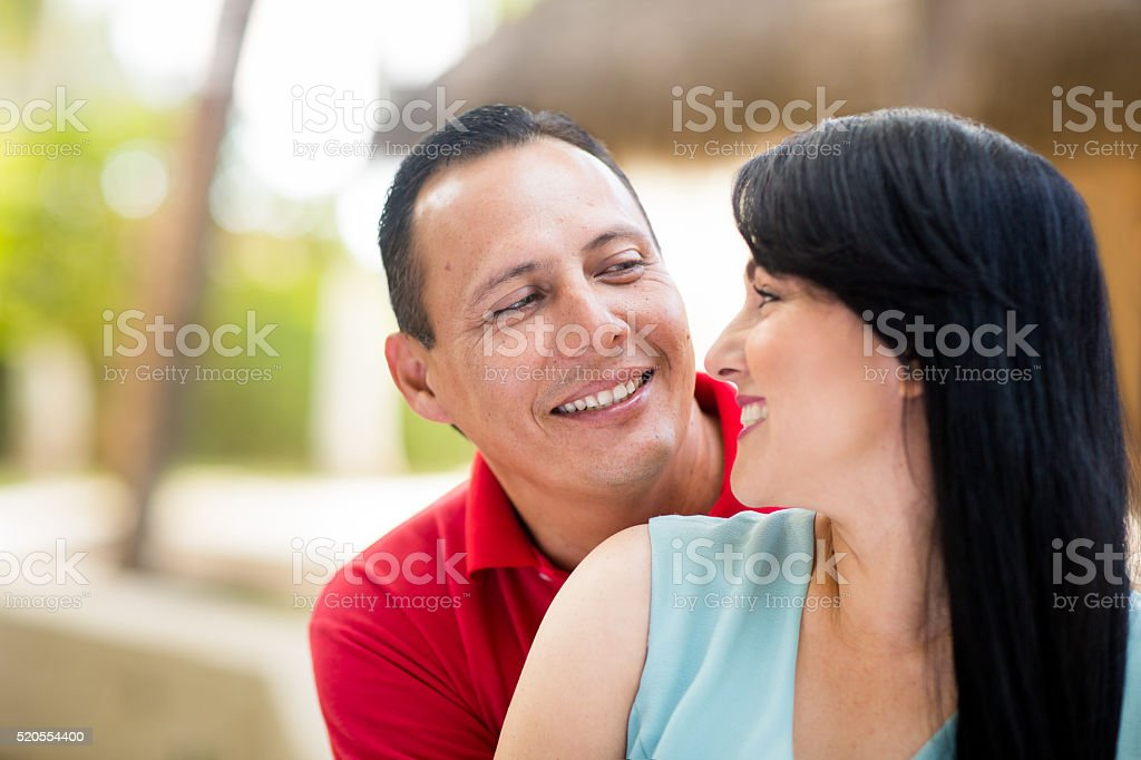 Lovely latin couple looking at each other and smiling stock photo