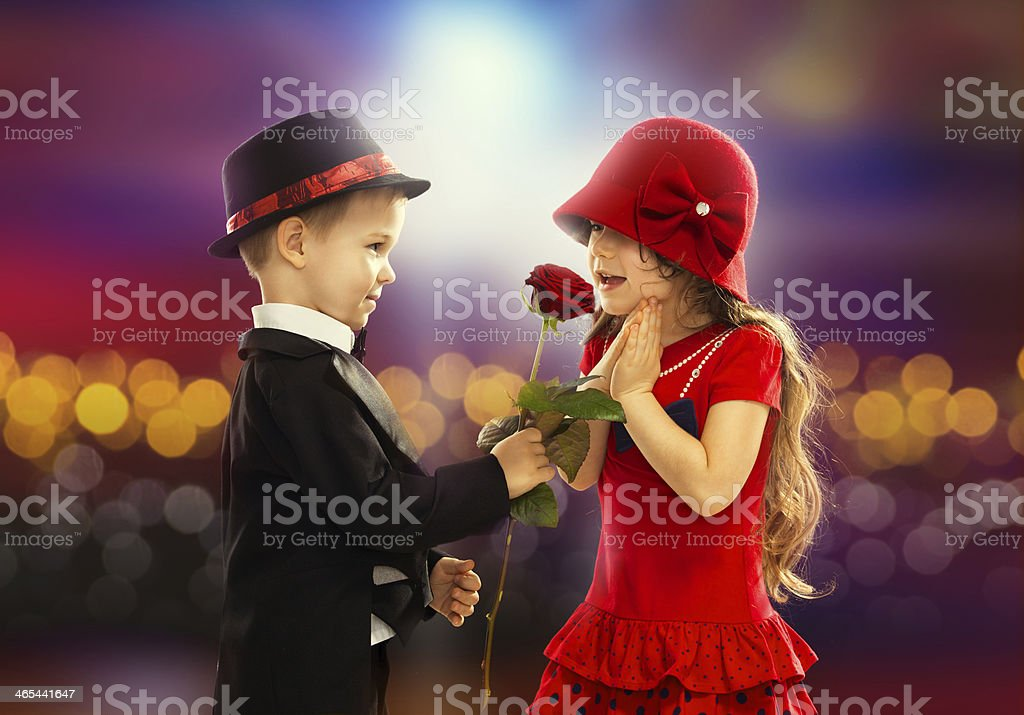 Lovely little boy giving  a rose to girl stock photo