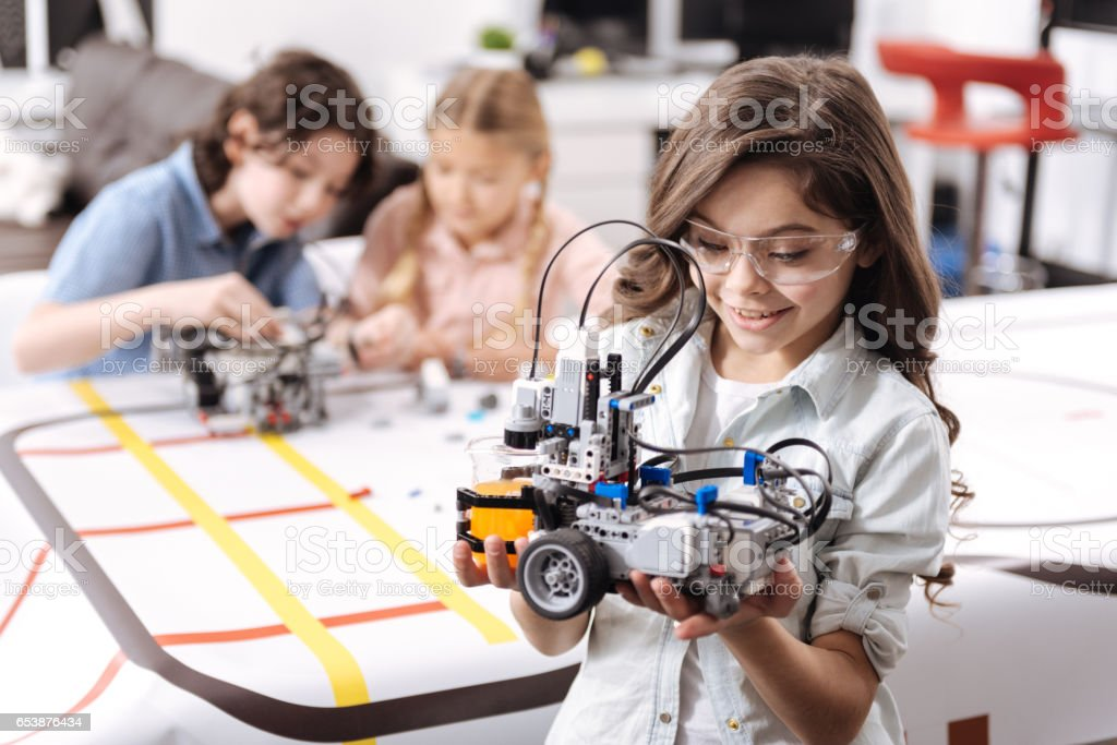 Lovely little girl holding robot at school stock photo