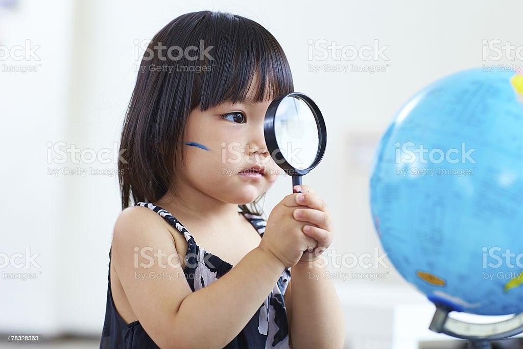 lovely little girl looking at globe royalty-free stock photo