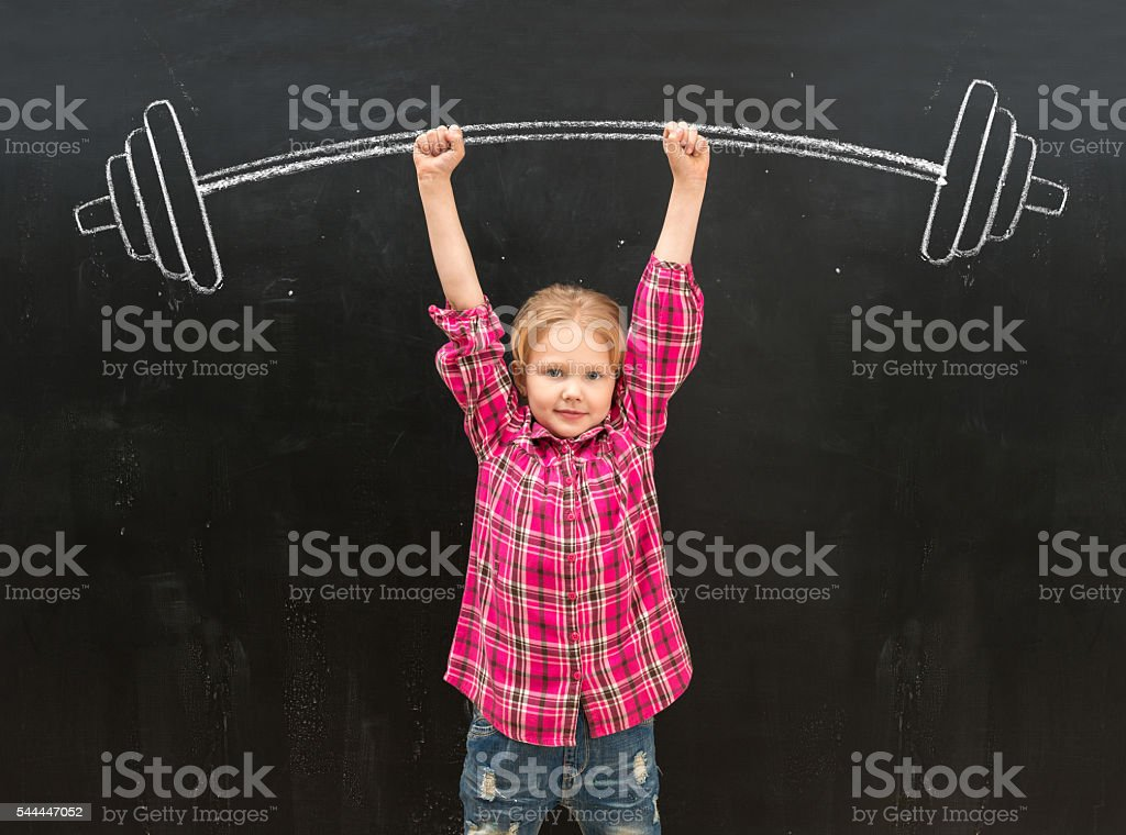 lovely little girl rising up drawm barbell with two hands stock photo