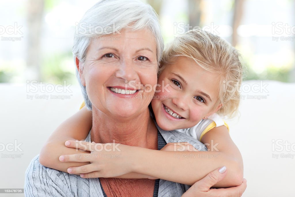 Lovely little girl with her grandmother looking at the camera stock photo