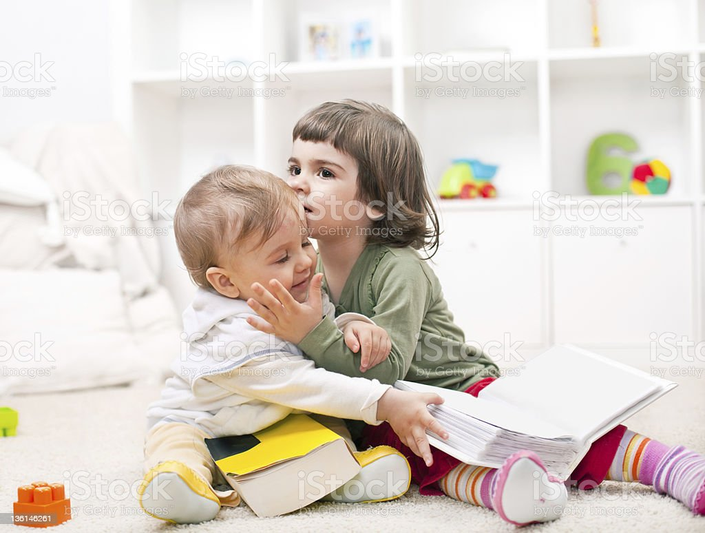 Lovely little sister embracing her baby brother royalty-free stock photo