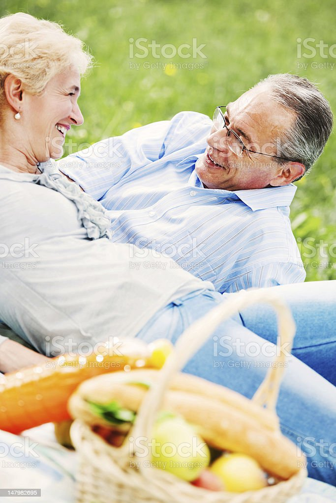 Lovely mature couple having a picnic in park. royalty-free stock photo