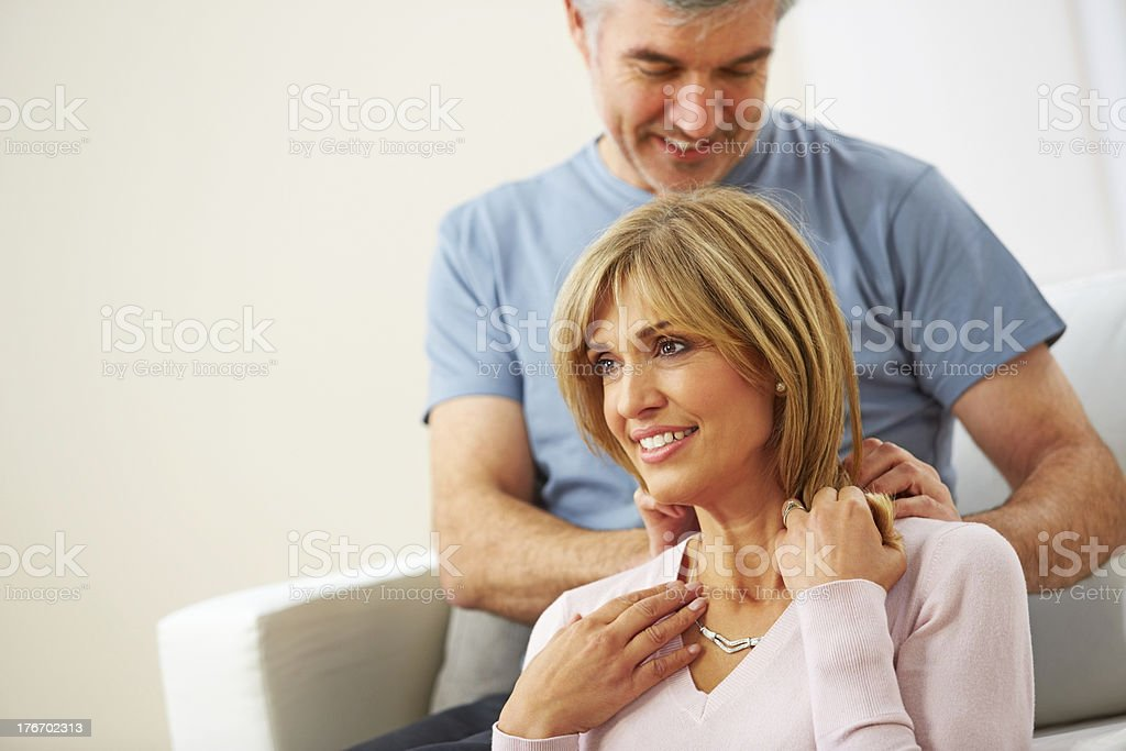 Lovely mature husband gifting necklace to his wife royalty-free stock photo
