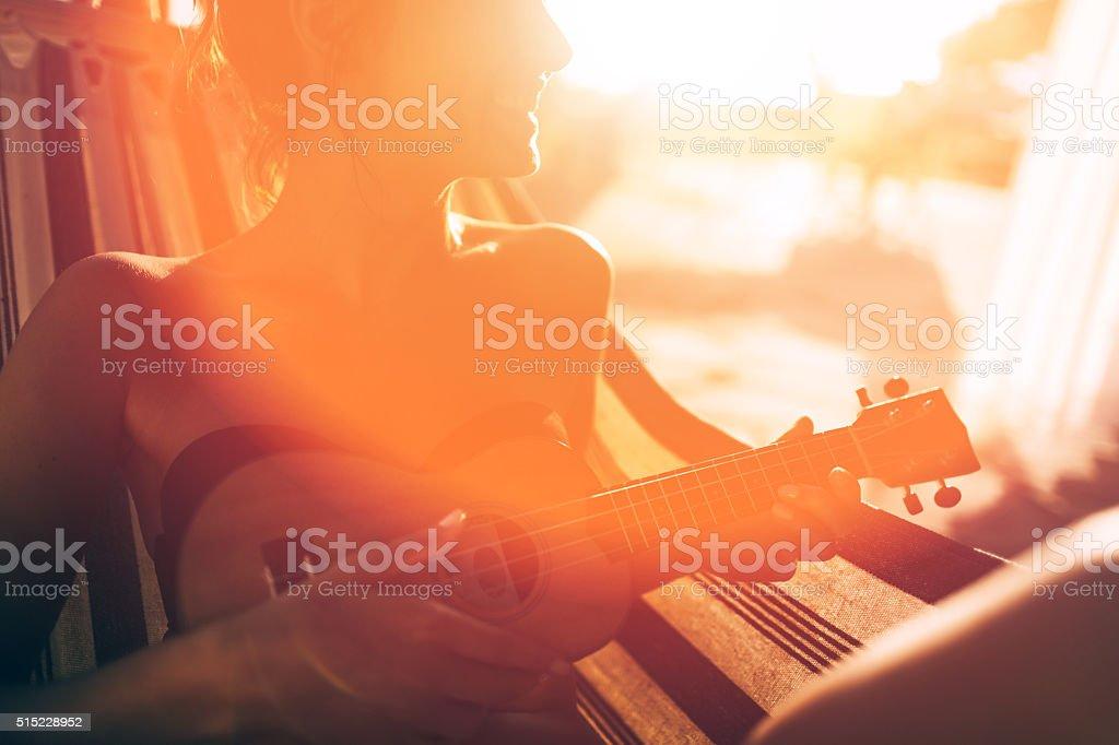 Lovely musician in the hammock stock photo