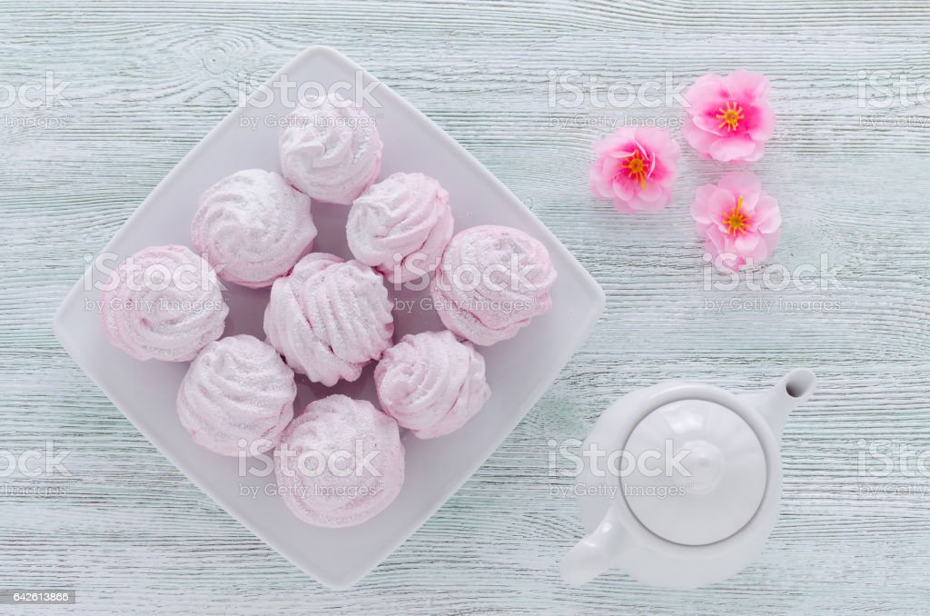 lovely pastel rose meringues, zephyrs, marshmallows and a coffee pot, flowers on the wooden vintage table stock photo