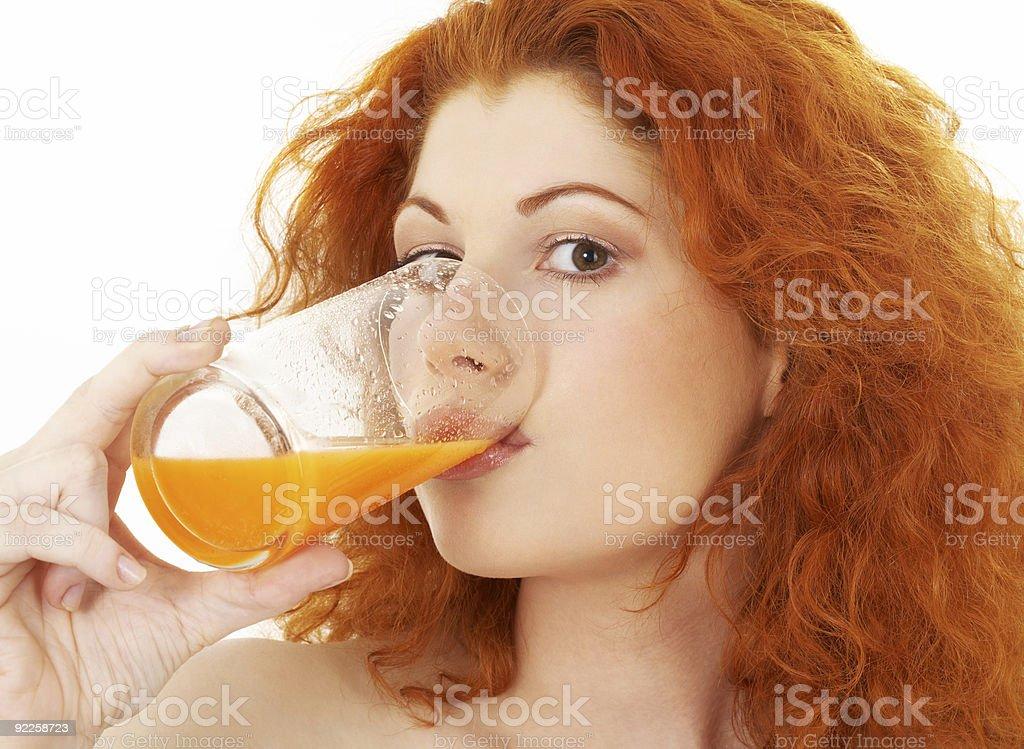 lovely redhead drinking orange juice stock photo