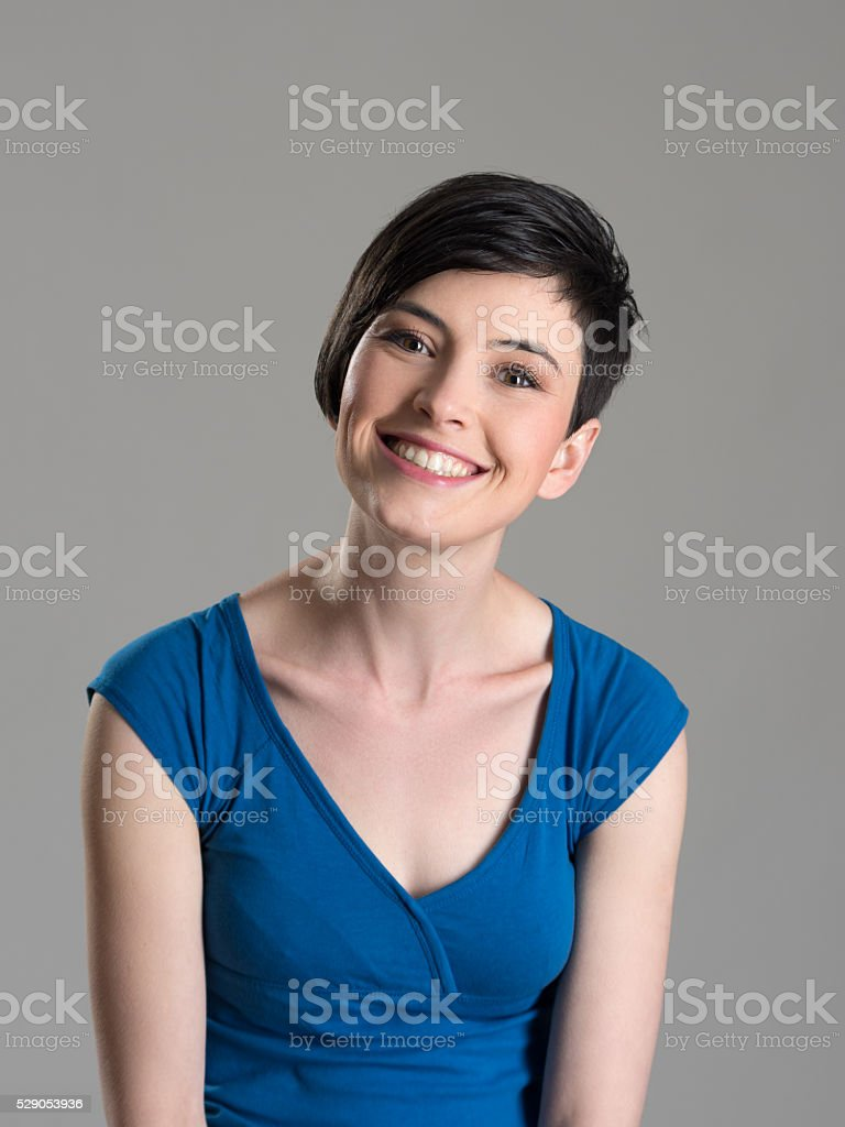 Lovely short hair brunette smiling at camera with tilted head stock photo