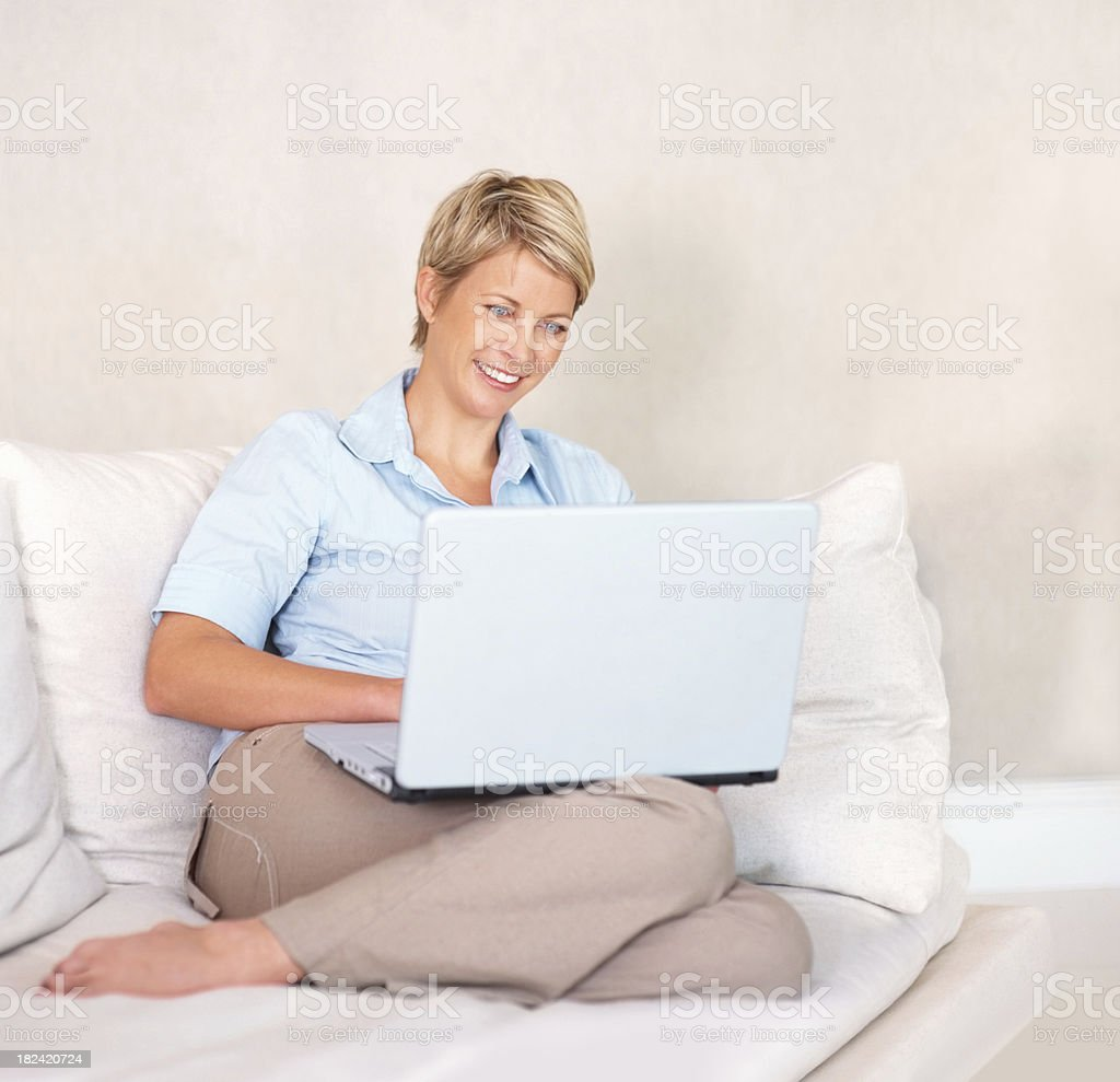 Lovely smiling woman sitting on couch using a laptop royalty-free stock photo
