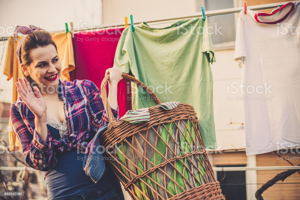 Lovely vintage style lady waving from her back yard stock photo