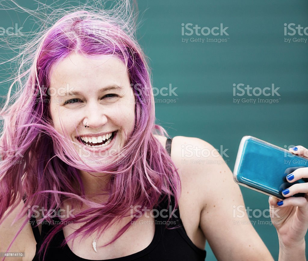 Lovely windblown girl with magenta hair takes smiling selfie stock photo