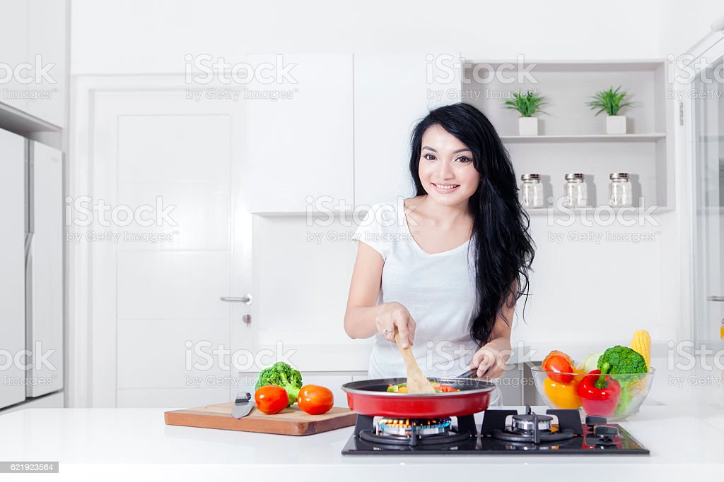 Lovely woman cooking while smiling stock photo