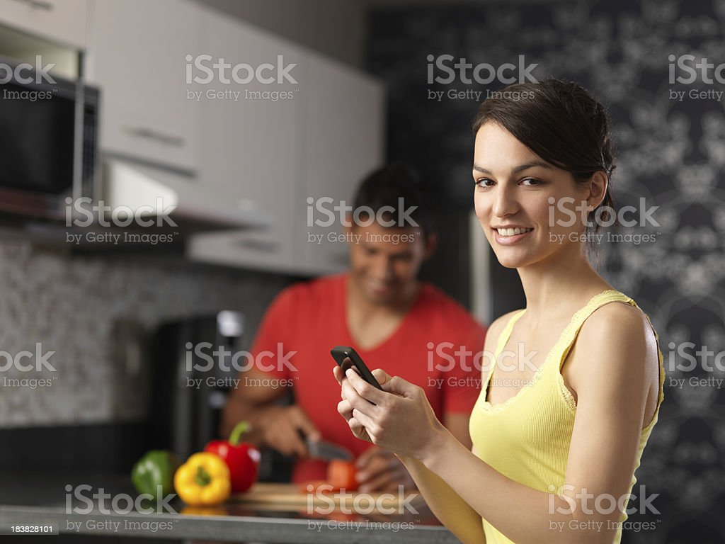 Lovely woman texting sitting in the kitchen royalty-free stock photo