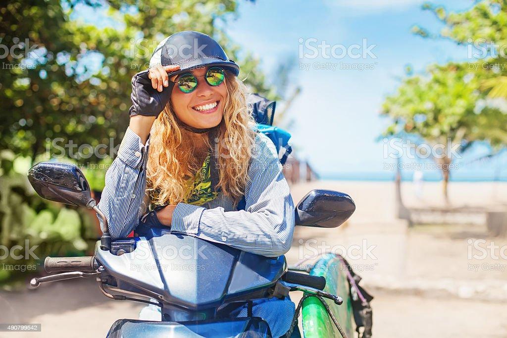 Lovely women sitting on motorbike with surfbord stock photo