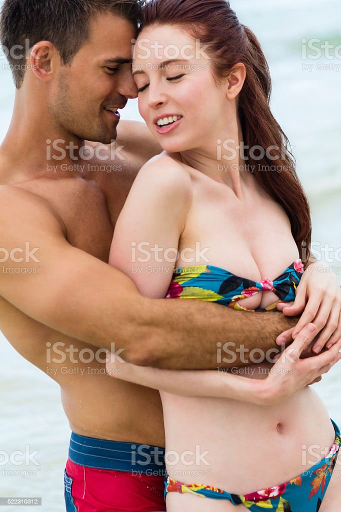 Lovely young couple embracing each other on beach, eyes closed stock photo