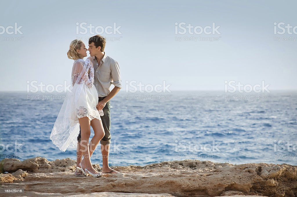 Lovely young couple kissing at the sea shore. royalty-free stock photo