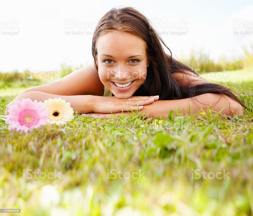 Lovely young female lying on grass field stock photo