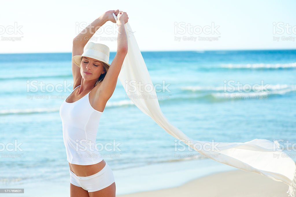 Lovely young female with a white shawl at the sea shore stock photo
