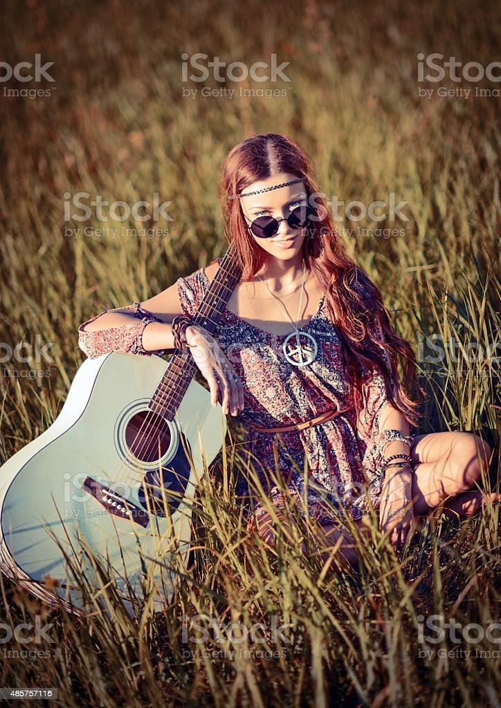 Lovely young hippie girl with guitar sitting on grass stock photo
