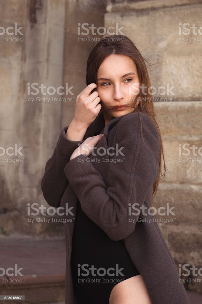 Lovely young woman in a coat at the city stock photo