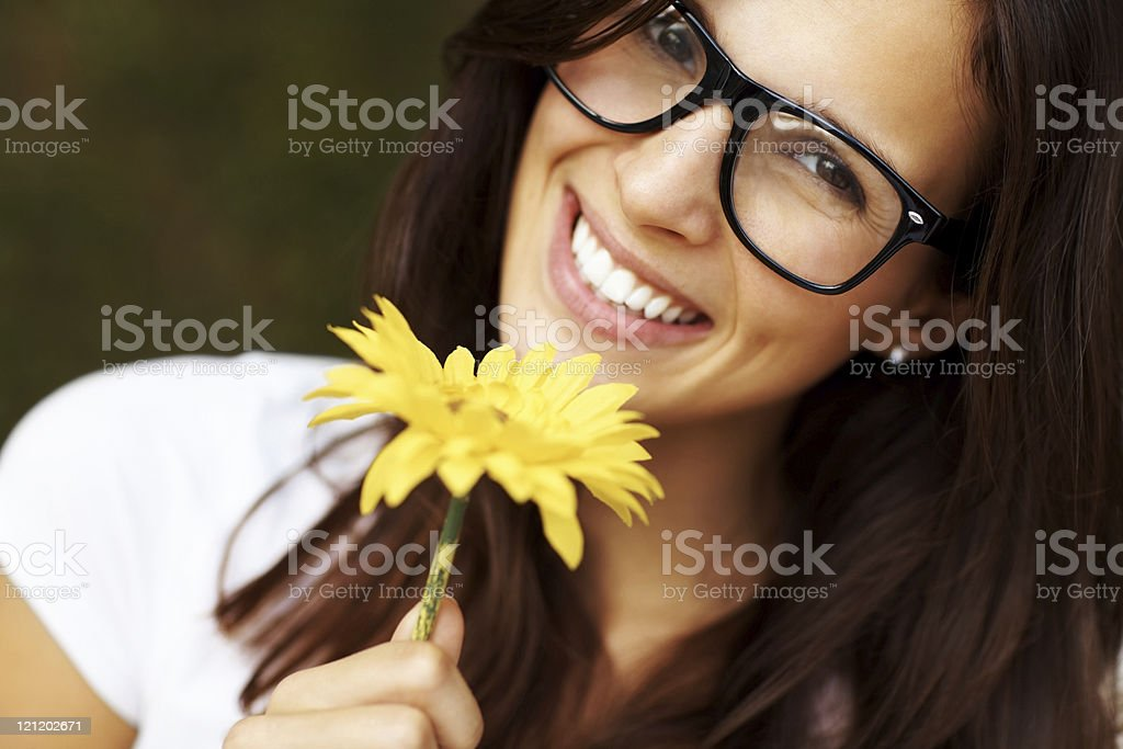 Lovely young woman in glasses holding a flower royalty-free stock photo