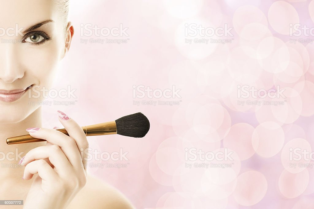 Lovely young woman with a make-up brush royalty-free stock photo