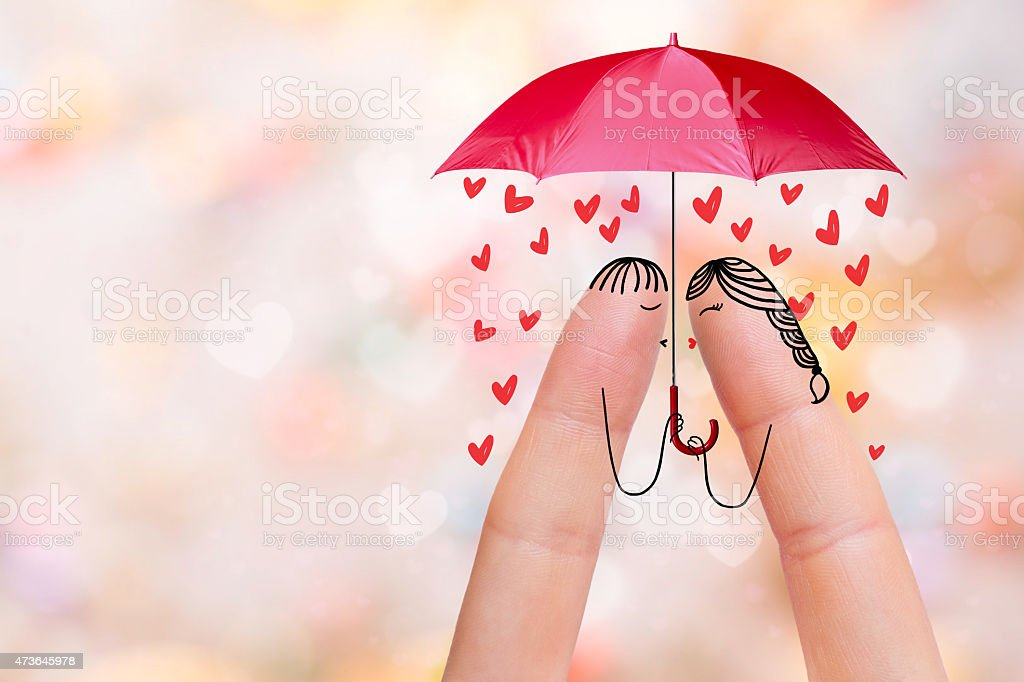 Lovers are kissing under umbrella with falling hearts stock photo