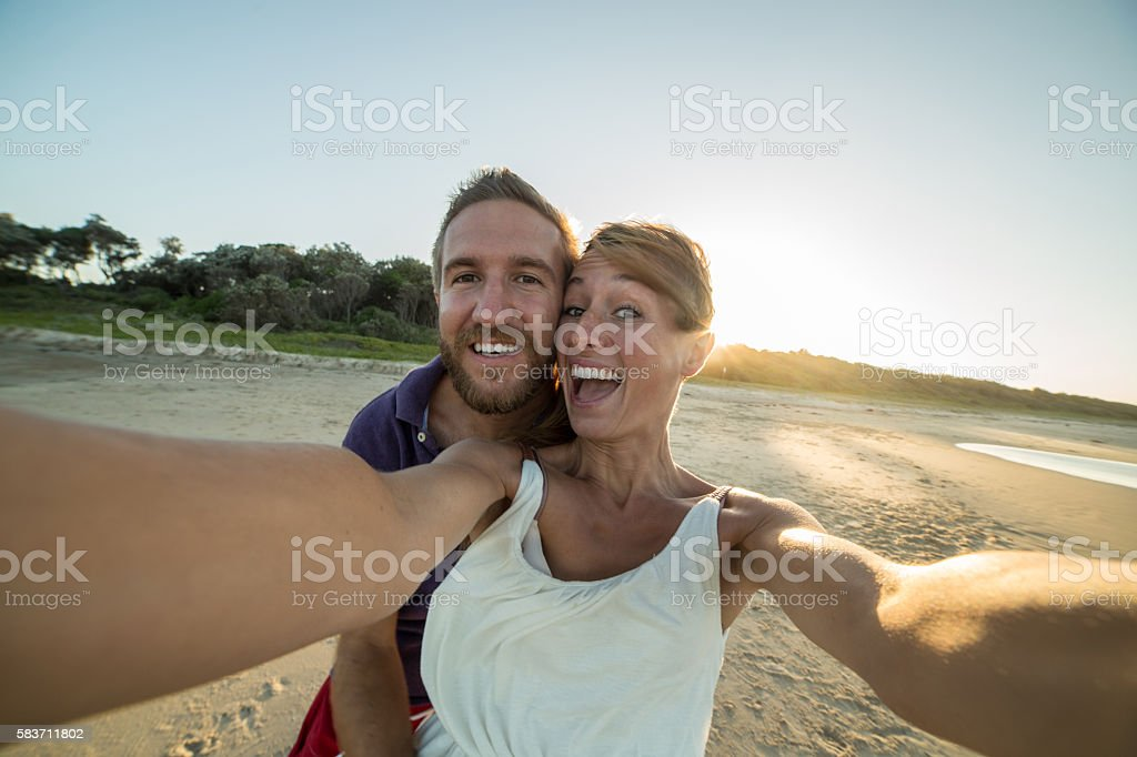 Lovers capturing summer holidays moments stock photo