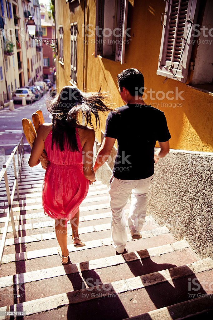 Lovers escaping with baguetts royalty-free stock photo