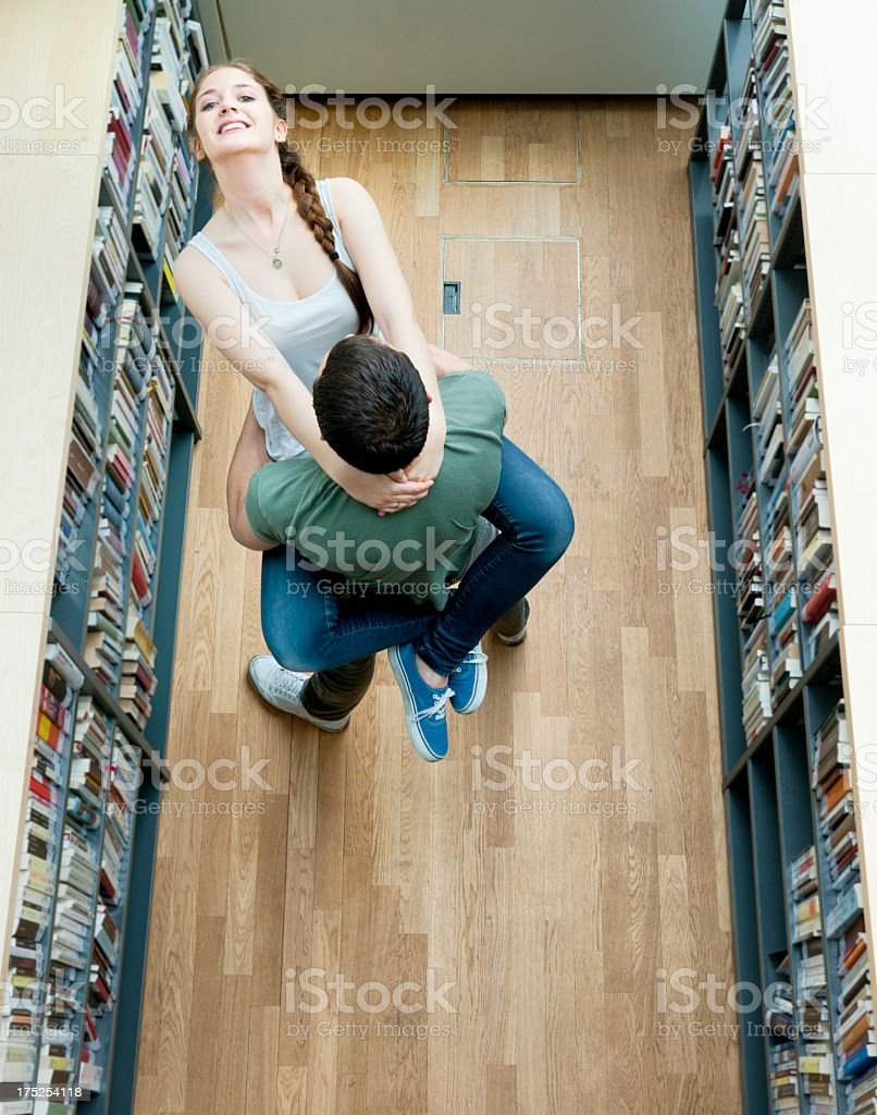 lovers in high school library stock photo