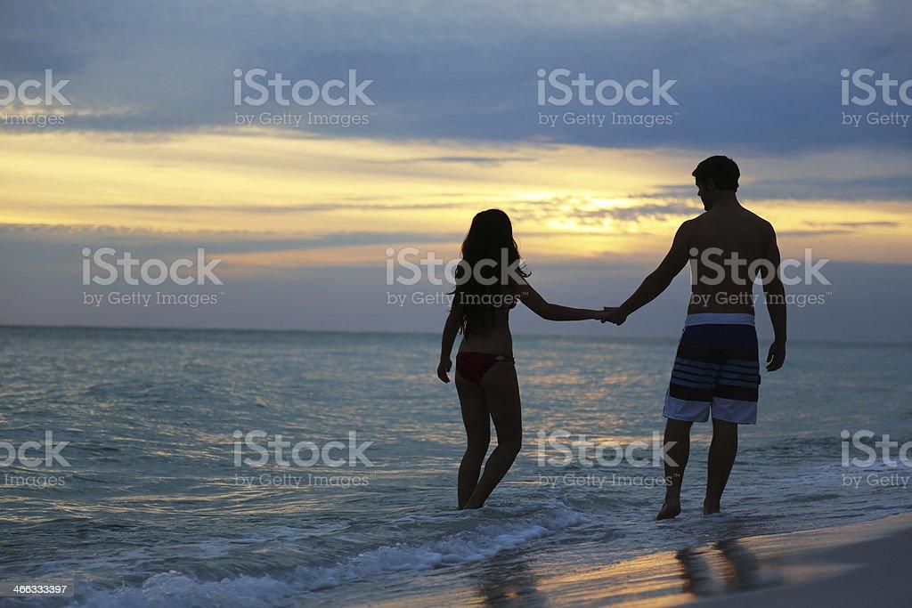 Lovers Romantic Walk on the Beach at Sunset stock photo