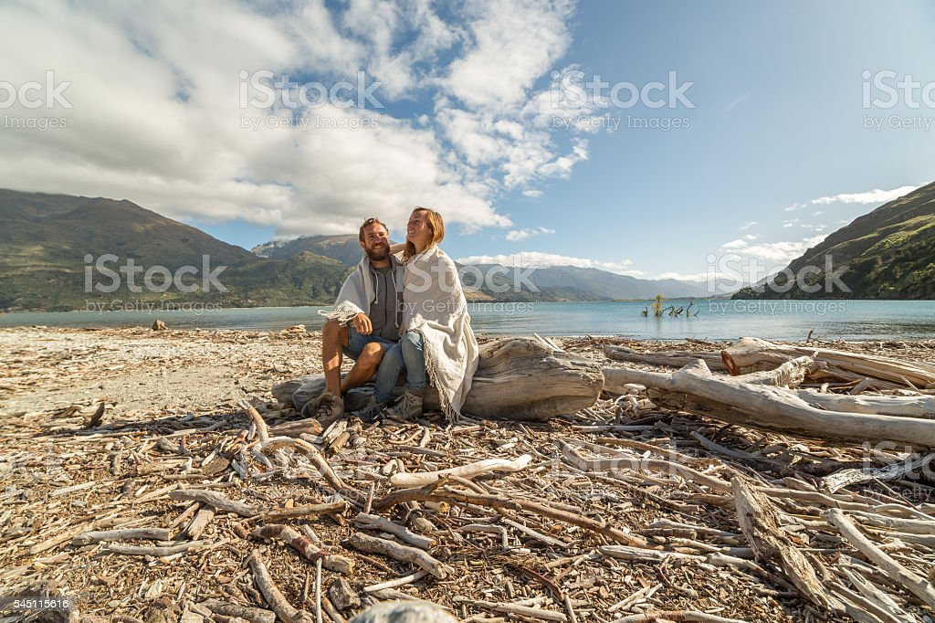 Lovers sitting on tree trunk by the lake stock photo