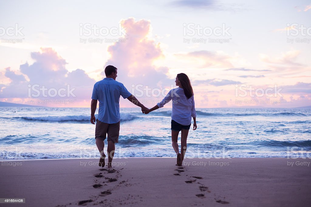 Lovers Walking on the Beach at Sunset on Vacation stock photo