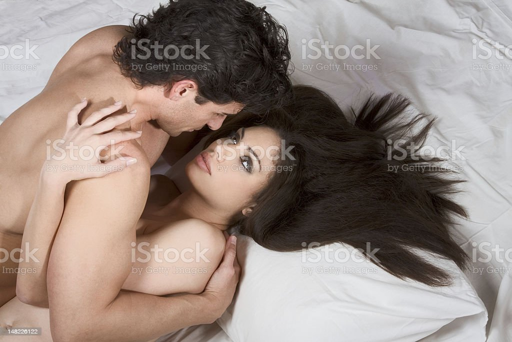 Loving affectionate nude heterosexual couple on bed making love royalty-free stock photo