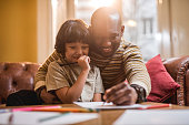 Loving African American father and son drawing together at home.