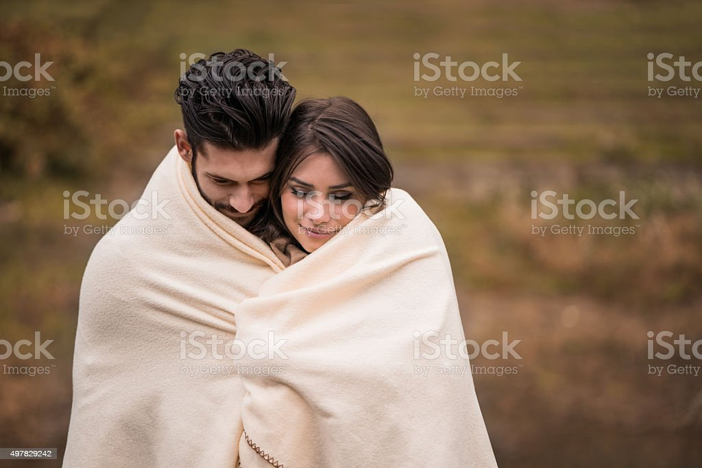 Loving couple covering with blanket while feeling cold outside. stock photo